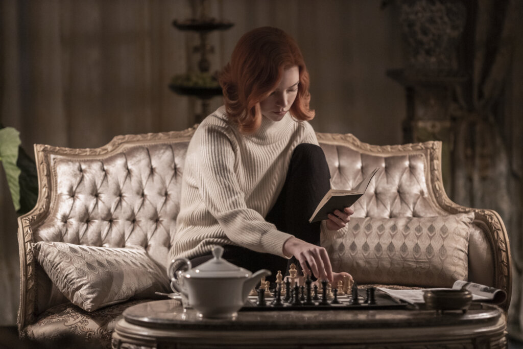 Beth sitting in chair playing chess
